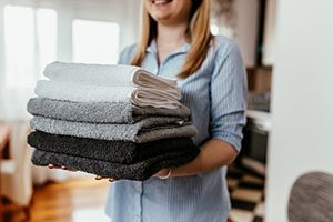 Young woman holding a pile of ironed clean towels.