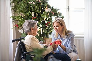 A health visitor and a senior woman in wheelchair with a present at home at Christmas time.