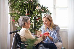 Une bénévole offre un cadeau à l'occasion des Fêtes à une personne en fauteuil roulant