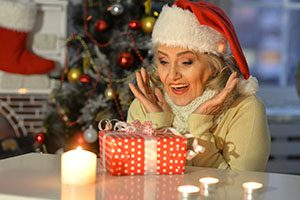 Portrait of happy senior woman with Christmas gift